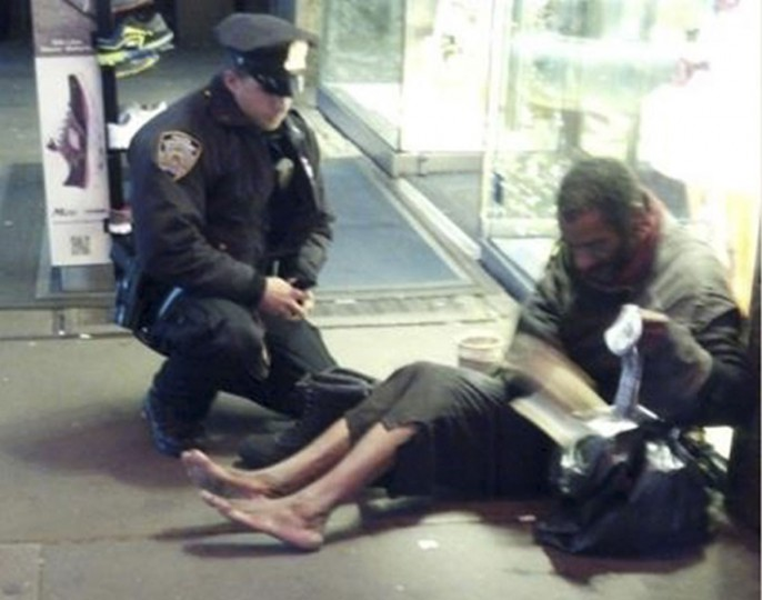 New York police officer Larry DePrimo gives a homeless man a pair of boots and socks in Times Square in this November 14, 2012. The photograph has drawn a deluge of praise after it was published on the police department's Facebook page this week. (Jennifer Foster/Handout/Reuters)