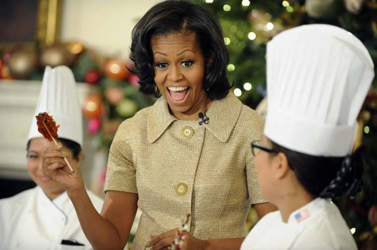 U.S. first lady Michelle Obama holds a candy as she welcomes military families, including Gold Star and Blue Star parents, spouses and children for the first viewing of the 2012 holiday decorations at the White House in Washington. (Mary F. Calvert/Reuters)