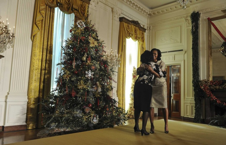 U.S. first lady Michelle Obama hugs a volunteer while presenting the holiday decorations at the White House in Washington. (Mary F. Calvert/Reuters)