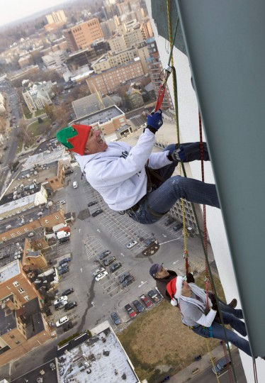 Bobby Valentine, former Boston Red Sox manager (R) and Brian Cashman, general manager of the New York Yankees rappel 22 stories from one of the tallest buildings in Stamford to mark the start of Santa's arrival as part of 'Heights & Lights' in Connecticut. (Michelle McLoughlin/Reuters)
