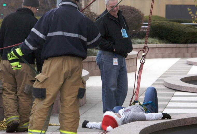 Brian Cashman, general manager of the New York Yankees, falls to the ground after rappelling 22 stories from one of the tallest buildings in Stamford to mark the start of Santa's arrival as part of 'Heights & Lights' in Connecticut. (Michelle McLoughlin/Reuters)