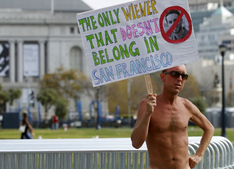 A nude man carries a sign at Civic Center Plaza in San Francisco, California October 30, 2012. (Robert Galbraith/Reuters)
