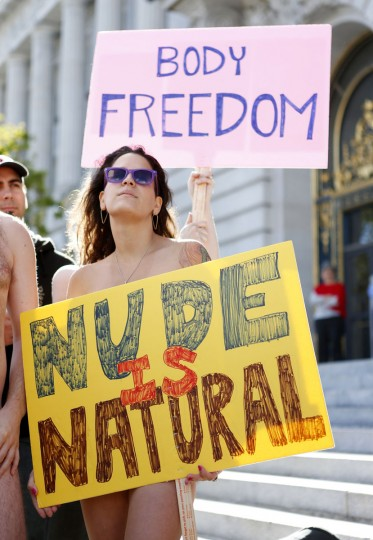 A woman, who would not give her name, holds a sign saying 'Nude is Natural,' during a rally against banning nudity in parts of the city in San Francisco, California, November 14, 2012. (Beck Diefenbach/Reuters)