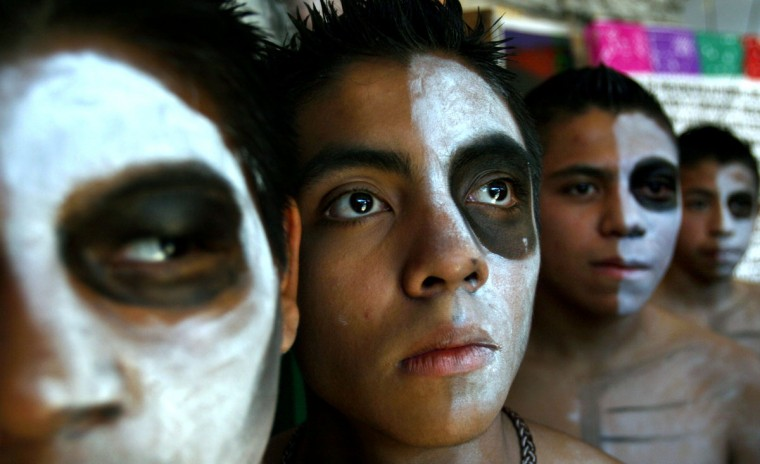 Young men with their faces painted, representing death, partake in day of the dead celebrations at the Zocalo square in Mexico City, Tuesday, Nov. 1, 2005. Mexicans honor their deceased loved ones on Nov. 1 and 2. (Marco Ugarte/AP Photo)