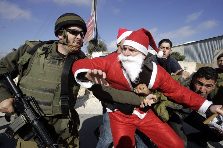An Israeli soldier tackles a Palestinian protester dressed as Santa Claus or Father Christmas during at a protest against Israel's separation barrier in the village of Umm Salamunah near the biblical West Bank town of Bethlehem, 21 December 2007. Israeli guards beat five demonstrators, including one dressed as Father Christmas, during a protest today against Israel's separation barrier in the West Bank, organisers said. (Musa Al-Shaer/AFP/Getty Images)