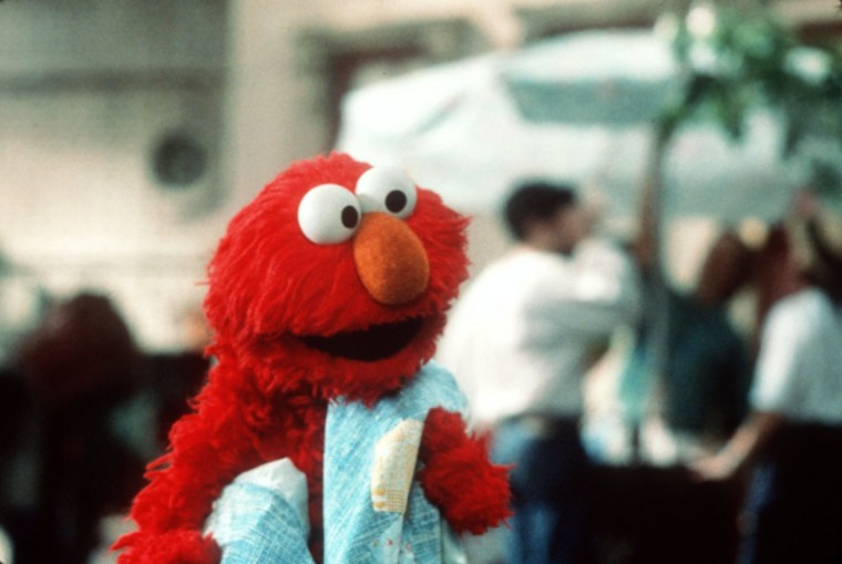 "With his cherished blue blanket at his side, Sesame Street's lovable monster Elmo makes his feature film debut in ""The Adventures of Elmo in Grouchland."" The movie was Sesame Street's second feature-length film after 1985's ""Sesame Street Presents Follow That Bird."" (James Bridges/Handout)"