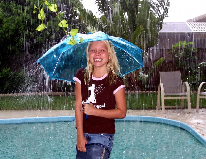 "Cyndi Ryan is this week's winner of the Reader SunShots category, ""April Showers,"" for her photo of 9-year-old Emily making the most out of sudden shower in Sarasota, Florida. Ryan used an old Kodak CX7430 point-and-shoot to make the image. Jerry Jackson, The Baltimore Sun's senior picture editor comments, ""Cyndi captured a moment of joy on what looks to be a pretty dreary day. Her use of fill flash with a slow shutter speed allowed the subject to stand out while still showing the movement of the downpour."""