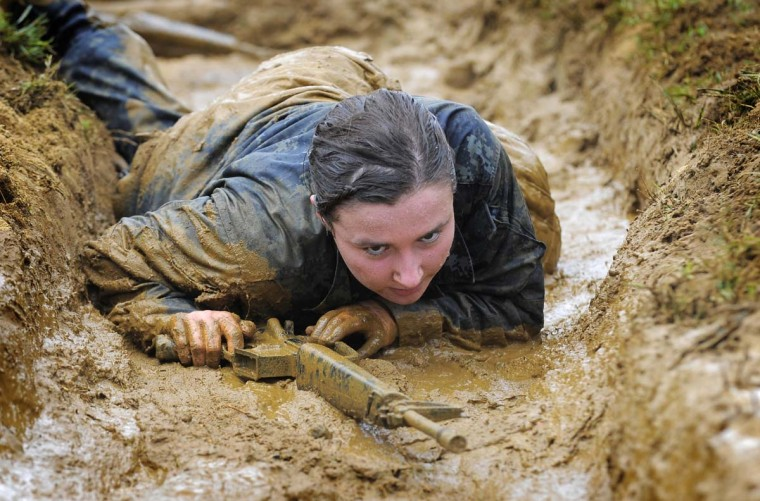 In 2012, Anna Eileen Dilks crawls through a muddy trench in the Wet and Sandy Drill, part of a 14-hour physical and mental training course and leadership challenge for Naval Academy plebes. (Lloyd Fox/Baltimore Sun)