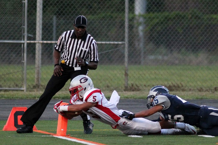 Glenelg's David Brookhart carries the ball across the goal line while Howard's Andrew Young, right, tries to stop him during the football game at Howard High School in Ellicott City on Friday, Aug. 31, 2012. (Jen Rynda/Baltimore Sun Media Group)