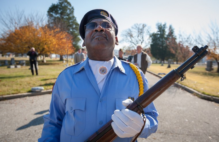 American Legion Post 60 member Rickey Witcher, of Laurel, holds a non-firing replica rifle after the ceremony, watching other members adjust the height of the American Flag. (Nate Pesce/Baltimore Sun Media Group)
