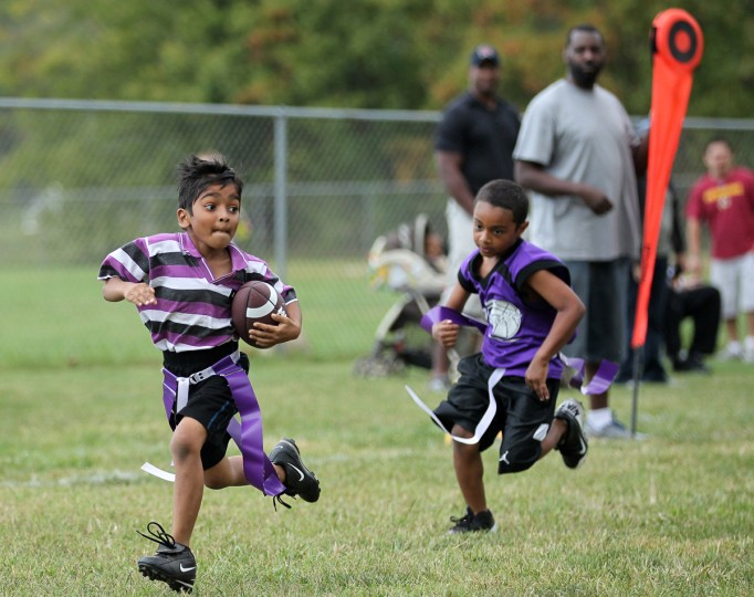 Vijay Maheswaran, left, 6, of Laurel runs the football in for a touchdown during the flag football game at Maryland City Park in Laurel on Saturday, Sept. 22, 2012. (Jen Rynda/Baltimore Sun Media Group)