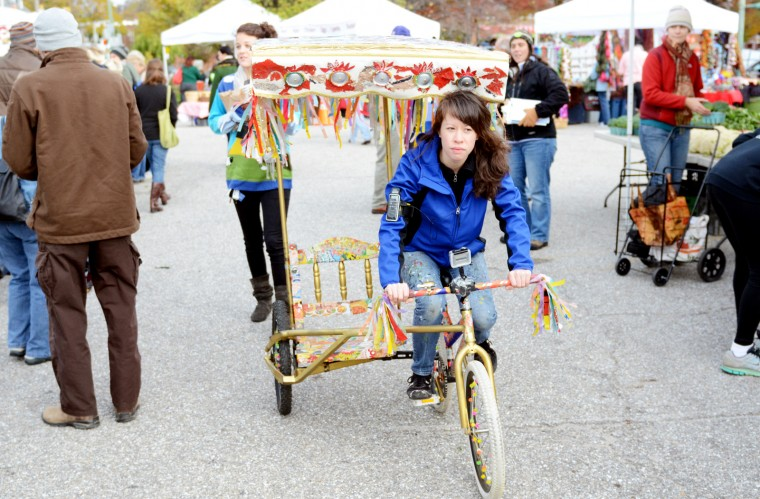 Michelle Nugent, a Charles Village resident and community arts student at MICA, rides her homemade pedicab through the crowd at the Waverly Farmer's Market on Saturday, Nov. 3, 2012. The goal of The Pedicab Project is to engage with different people and learn about Baltimore. (Jon Sham/Patuxent Homestead)