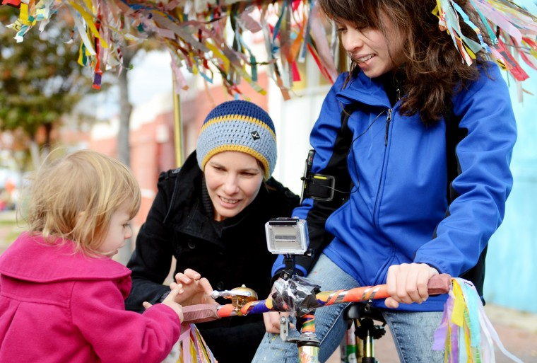 Michelle Nugent lets 3-year-old Alsa ring the bell on her pedicab after giving her and her mother Lauren Going, center, a ride. (Jon Sham/Patuxent Homestead)
