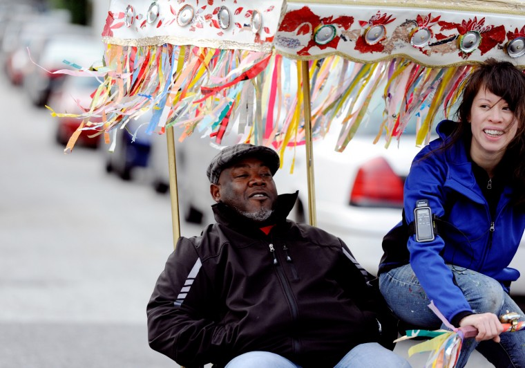 Nugent laughs with Eric Rogers of Towson while giving him a ride on her pedicab. (Jon Sham/Patuxent Homestead)