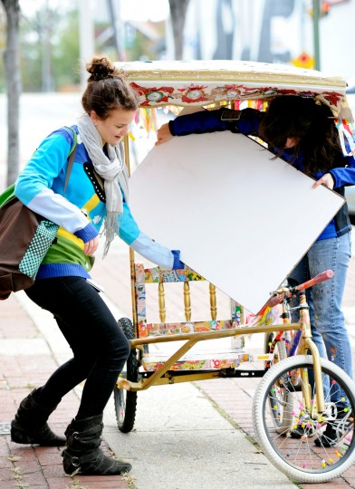 Nugent's friend and housemate Beth Mendenhall, left, helps her put the sign in the pedicab before the two of them make the trek back to Charles Village after two successful interviews. (Jon Sham/Patuxent Homestead)