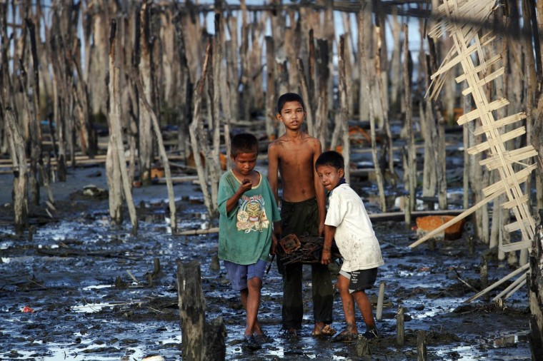 Boys walk through mud carrying items salvaged from the ruins of the burned neighbourhood in East Pikesake ward in Kyaukphyu. Picture taken November 5. (Minzayar/Reuters)