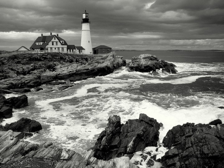"The winner of this week's Reader SunShots series ""Black and White"" is Lynda Folck for her picture of the oldest lighthouse in Maine, the Portland Head Light. She took the picture with a Sony DSC-H50 following a rainstorm and high tide. Here is a critique by Robert Hamilton director of photography. ""This is a great example of a picture that is better in black and white than in color. As a grayscale image the content of the photograph works harmoniously with the powerful storm clouds and the angry seas breaking against the shoreline. The photographer did a great job of composing the picture by offsetting the lighthouse. This is a photograph I'd love to hang on my wall."""