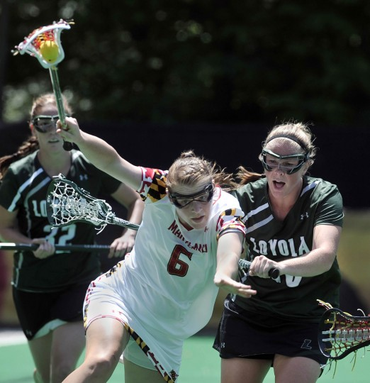 Kelly McPartland, center, of Maryland, keeps control of the ball under pressure from Ashley Moulton, right, of Loyola, in the first half of a women's lacrosse NCAA quarterfinal. Maryland wins 17-11. (Kim Hairston/[Baltimore Sun)