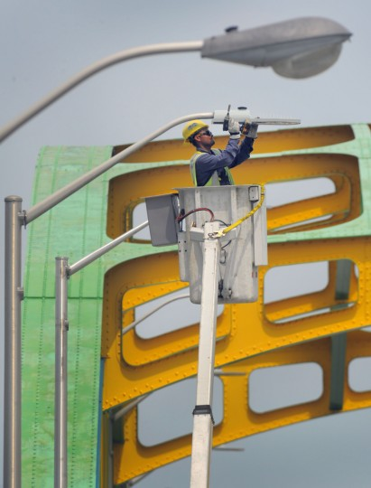 Marvin Cabrera, working for the Baltimore City Dept. of Transportation's street light conversion, installs an LED lamp as the truck slowly makes its way on the Howard Street Bridge, replacing sodium vapor street lamps with lower-profile, higher-efficiency LED (Light emitting diode) street lamps. The crew says that Baltimore is phasing out its utilization of the orange-colored sodium vapor lamps (seen in foreground, above) throughout the city. (Karl Merton Ferron/Baltimore Sun)