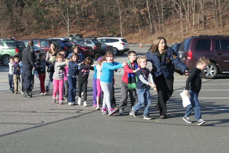 State police personnel lead children from the Sandy Hook Elementary School in this handout picture from the Newtown Bee, in Newtown, Connecticut. All public schools in Newtown, Connecticut, were placed in lockdown on Friday following a shooting at Sandy Hook Elementary School. (Newtown Bee/Shannon Hicks/)