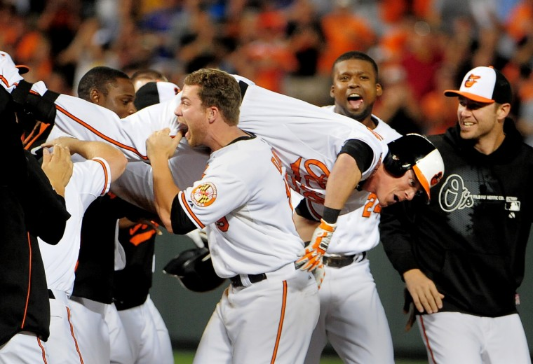 Teammates mob Nate McLouth after he hit the game winning RBI single which scored Manny Machado to give Baltimore the 3-2 win over the Tampa Bay Rays. Chris Davis lifted him up at 2nd base and carried him around the field. (Gene Sweeney Jr./Baltimore Sun)