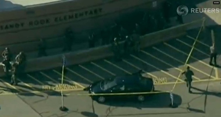 Police tape off an area around a car after a shooting at Sandy Hook Elementary School in Newtown, Connecticut. (WNBC/via Reuters)