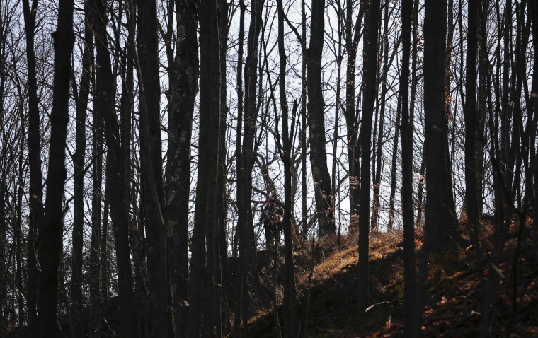A police officer keeps guard from a hill top over looking Sandy Hook Elementary School after a shooting in Newtown, Connecticut. At least 27 people, including children, were killed on Friday when at least one shooter opened fire at an elementary school in Newtown, Connecticut, CBS News reported, citing unnamed officials. (Adrees Latif/Reuters photo)