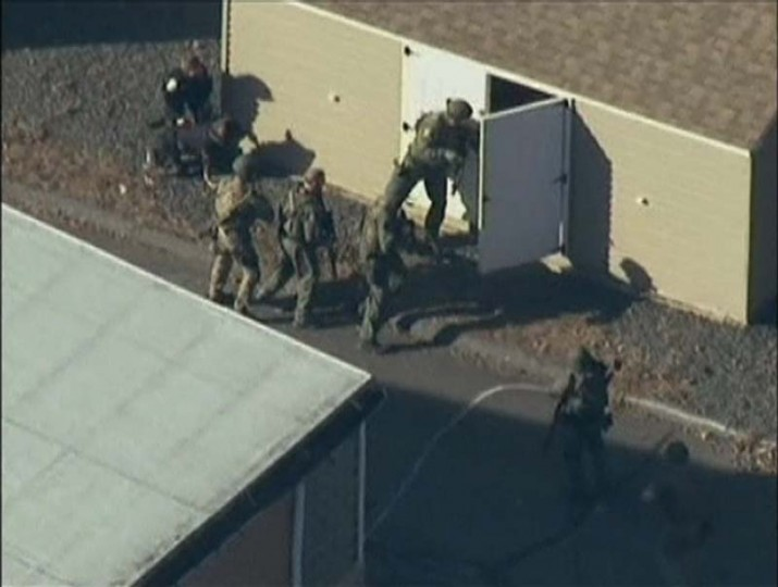 Police search a building after a shooting at Sandy Hook Elementary School in Newtown, Connecticut. (WNBC/via Reuters)