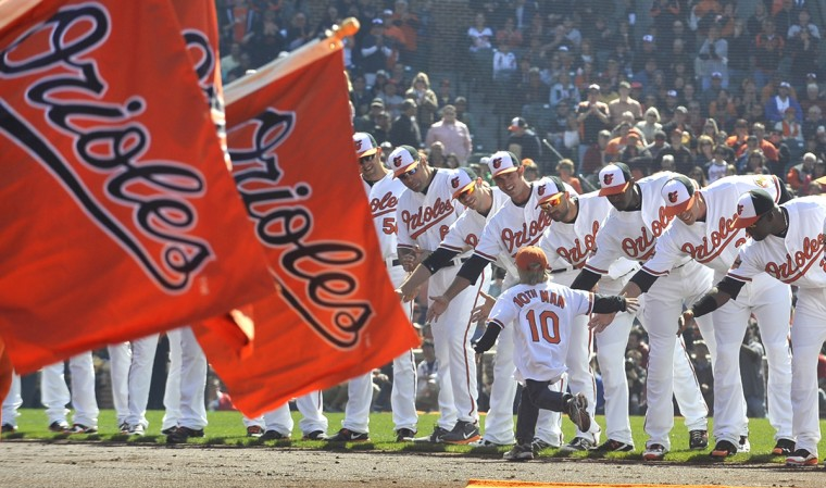 Orioles' players greet the 10th Man, Connor Schoenwetter, 5, of Cockeysville, during the opening day ceremonies. Baltimore Orioles vs. Minnesota Twins on opening day baseball at Camden Yards. (Lloyd Fox/Baltimore Sun)