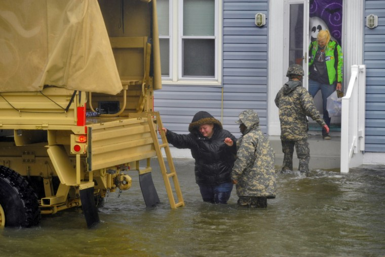 A military truck sits in the water on St. Louis Avenue between 8th and 9th Streets in Ocean City, MD, as personnel help residents evacuate with their essential belongings from their apartment as Hurricane Sandy, now a Category One system, floods the streets. (Karl Merton Ferron/Baltimore Sun)