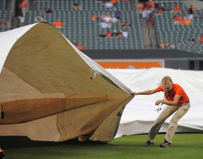 Head groundskeeper Nicole Sherry shouts for assistance to reel back in the tarp which got caught by winds, pushing some of it to second base, as the grounds crew has some difficulty keeping it down, during wind gusts from a nearby passing storm at Oriole Park at Camden Yards. (Karl Merton Ferron/Baltimore Sun)