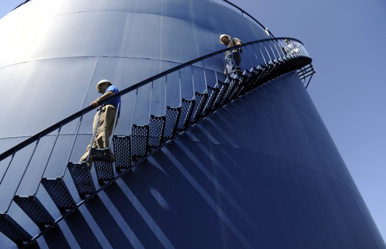 Dominion employees Dan Donovan, left, and Tim Nelson descend a water tank at the Dominion Cove Point terminal, which is a liquid natural gas (LNG) importing facility. The company hopes to build a liquifaction operation there so it can begin exporting LNG from the terminal. (Barbara Haddock Taylor/Baltimore Sun)