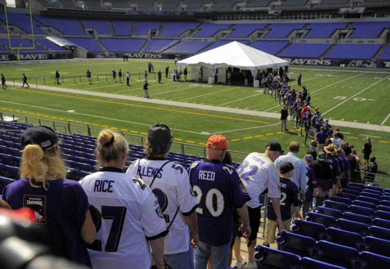 Wearing the Ravens colors at the family's rerquest, a stream of fans wait in line to pay respects at a public viewing of Art Modell, the onetime owner of the Baltimore Ravens, as he lies in a closed casket at the center of the field at the Ravens' stadium Saturday, Sep 8, 2012. (Karl Merton Ferron/Baltimore Sun)