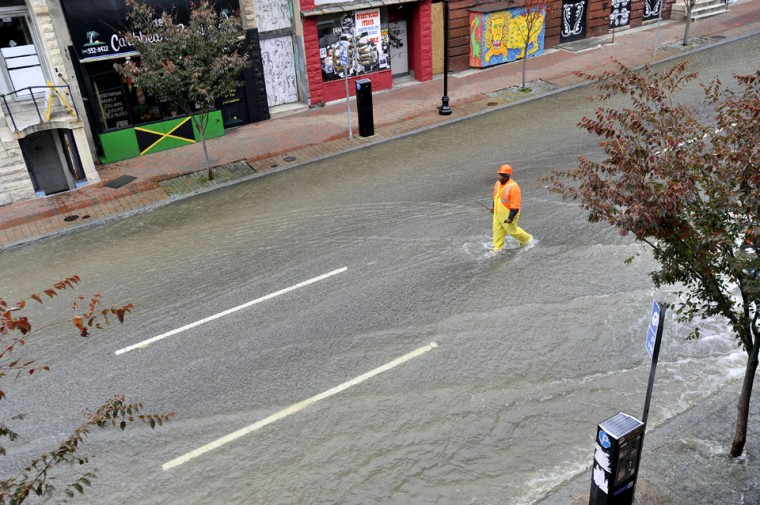 Nov. 8: All wet: Al Greene, Supervisor II, Bureau of Water and Wastewater, Department of Public Works, walks through flowing water in the 1800 block of N. Charles Street. The water is from a ruptured 60-inch transmission pipe at East 20th and North Charles streets. (Kim Hairston/Baltimore Sun)