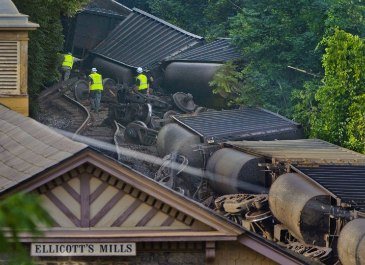 Three CSX employees navigate the debris and wreckage of the toppled hopper cars at the scene of a train derailment on a rail line that snakes along the Patapsco River at the Main Street overpass in historic Ellicott City. Two people were confirmed killed in the mishap as investigators sift through the wreckage, while interviewing witnesses to rebuild a timeline of events. (Karl Merton Ferron/Baltimore Sun)