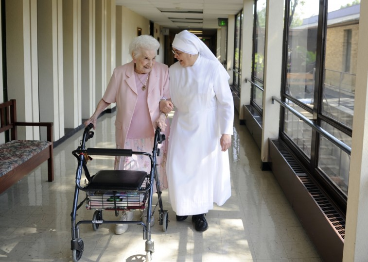 Rose Dente, left, is a 101 year old resident of St. Martin's Home, which a residence for elderly people that is run by the Little Sisters of the Poor. Here, Rose shares a laugh while walking down a hall with Sister Lourdes. (Barbara Haddock Taylor/Baltimore Sun)