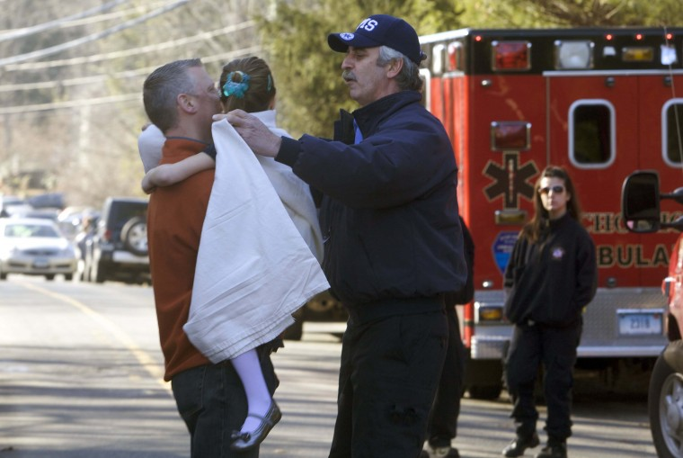 A young girl is given a blanket after being evacuated from Sandy Hook Elementary School following a shooting in Newtown, Connecticut. (Michelle McLoughlin/Reuters photo)