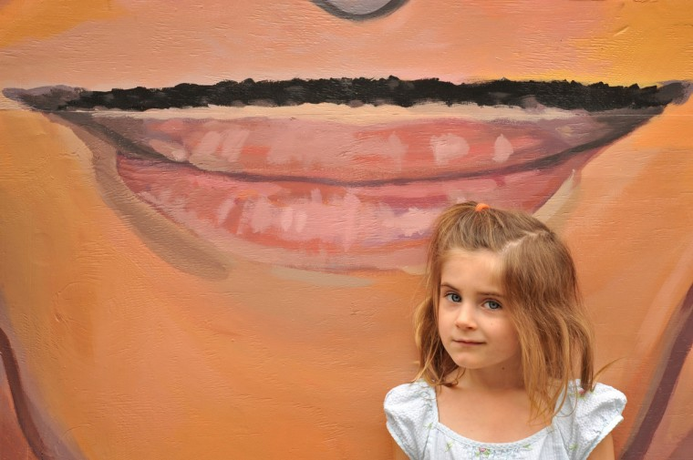 Melody Fowler, 4, of Westminster, poses with the 11 ft. 9 inch John Waters cut-out, on display in front of the Charles Theatre during the final day of Artscape. (Amy Davis/Baltimore Sun)