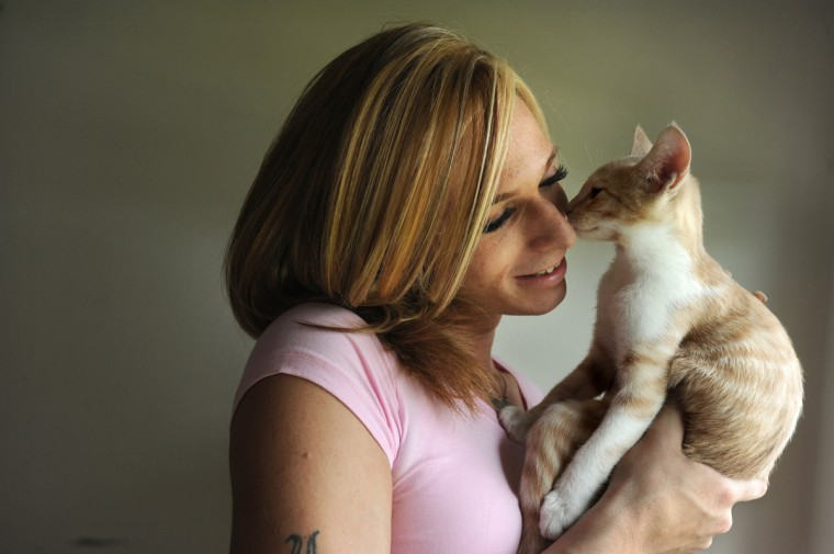 Chrissy Lee Polis, a transgender woman, gets a smooch from Tye, one of her two cats. One year ago, she was beaten in McDonald's for using the women's restroom. Algerina Perna/Baltimore Sun)