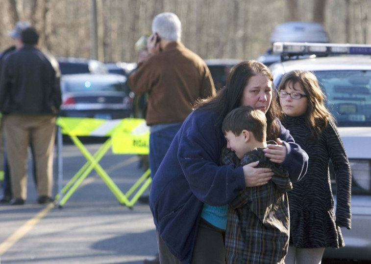 A young boy is comforted outside Sandy Hook Elementary School after a shooting in Newtown, Connecticut. A shooter opened fire at the elementary school in Newtown, Connecticut, on Friday, killing several people including children, the Hartford Courant newspaper reported. (Michelle McLoughlin/Reuters photo)