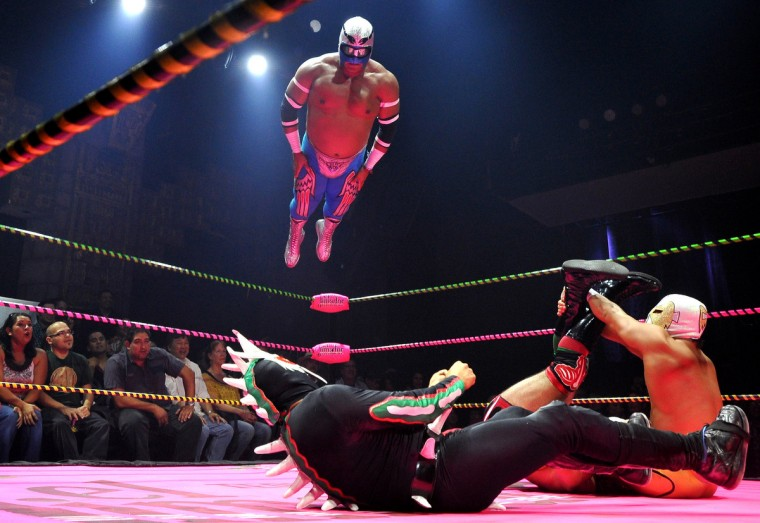 """Wrestlers perform during the Lucha Va Voom's Cinco de Mayan show at the Mayan Theatre in downtown Los Angeles, California on May 04, 2012. Lucha Va Voom is the mixture of elements of Lucha libre, or masked Mexican professional wrestling, with comedy and striptease. Since 2002, the company has toured the US. For the annual Cinco De Mayo show, they have added some more """"traditional"""" Mexican elements like Folklorico dancers, mariachis, Aztec dancers, tequila, and something called """"tamales from outer space."""" (Joe Klamar/Getty Images)"""