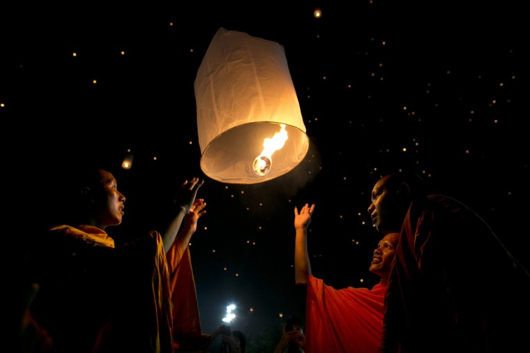 Thai monks light a lantern and release it to the night sky during celebrations to pay respect to Thailand's King Bhumibol Adulyadej on his 85th birthday in Bangkok, Thailand. King Bhumibol took the throne in 1946, making him the world's longest reigning monarch and the world's longest serving head of state. Yellow represents Monday, the birthday of the King. (Paula Bronstein/Getty Images)