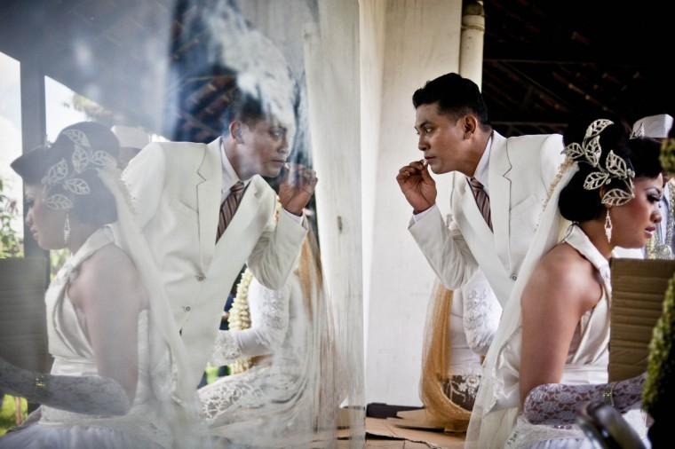 A groom prepares for his own wedding as he gets ready to take part in a mass Wedding ceremony in Yogyakarta, Indonesia. Twelve couples participated in a mass wedding as today saw a surge in marriage across the globe to mark the once in a century date of 12/12/12. (Ulet Ifansasti/Getty Images)