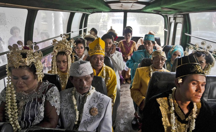 Brides and grooms sit on a bus before they get ready to take part in a mass Wedding ceremony in Yogyakarta, Indonesia. Twelve couples participated in a mass wedding as today saw a surge in marriage across the globe to mark the once in a century date of 12/12/12. (Ulet Ifansasti/Getty Images)