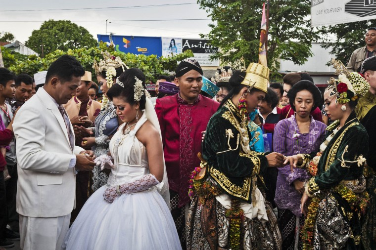 Brides and grooms exchange rings during a mass wedding ceremony in Yogyakarta, Indonesia. Twelve couples participated in a mass wedding as today saw a surge in marriage across the globe to mark the once in a century date of 12/12/12. (Ulet Ifansasti/Getty Images)