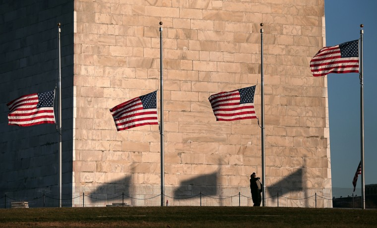 "A National Park Service employee lowers flags at the base of the Washington Monument to half staff after President Barack Obama ordered the action while speaking on the shootings at the Sandy Hook Elementary School. Obama called for ""meaningful action"" in the wake of the latest school shooting that left 27 dead, including 20 children. (Win McNamee/Getty Images)"