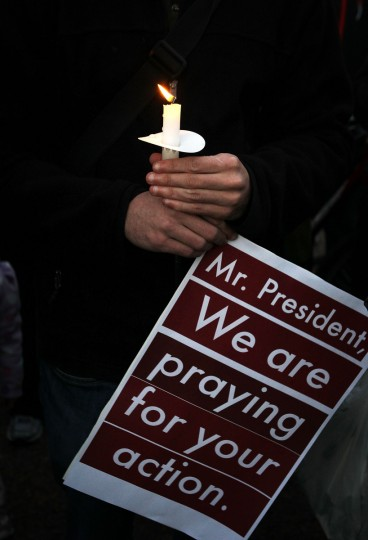 A man participates in a candle light vigil outside the White House to remember the victims at the Sandy Hook Elementary School shooting in Newtown, Connecticut. (Alex Wong/Getty Images)
