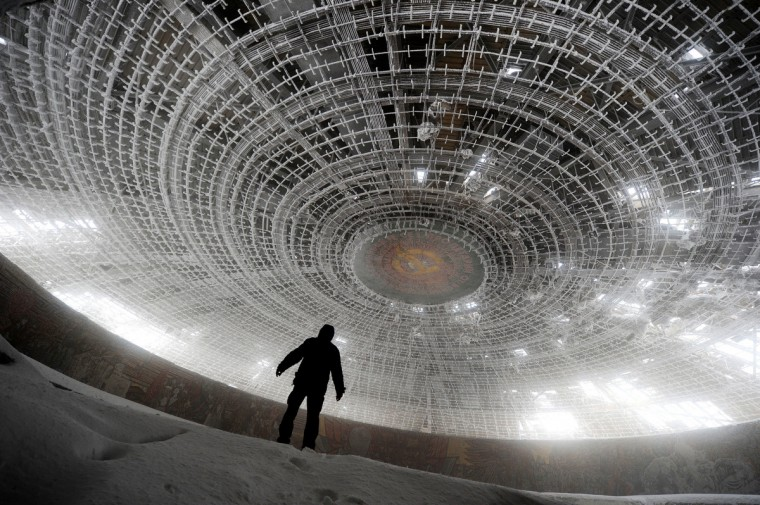 A man walks inside of the crumbling oval skeleton of the House of the Bulgarian Communist Party on mount Buzludzha in central Bulgaria on March 14, 2012. Over two decades after the toppling of the regime they glorified, the megalomaniac monuments of the communist era are still standing, setting a quandary for Bulgarian authorities, who can neither maintain nor dismantle them. (Dimitar Kilkoff/Getty Images)