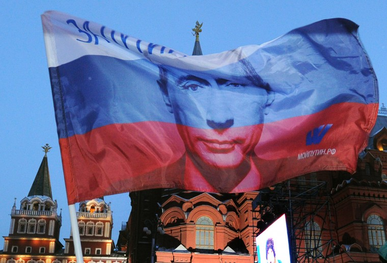 A Russian flag featuring Prime Minister Vladimir Putin flies above his supporters as they celebrate Putin's victory as they rally at the central Manezhnaya Square just outside the Kremlin in Moscow, March 5, 2012. Police said that some 15,000 people were taking part in a rally in support of the Russian strongman outside the Kremlin walls. (Alexander Nemenov/Getty Images)