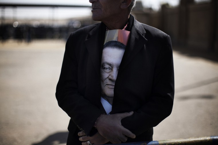 A supporter of ousted Egyptian president Hosni Mubarak (portrait) waits for news from his trial outside the court in Cairo on February 22, 2012, as the landmark murder and corruption trial of the former leader entered its final day of hearings, with the judge expected to announce the date of the verdict. Cameras are not allowed inside the courtroom and state television did not show Mubarak or the defendants arriving in court. (Marco Longari/Getty Images)